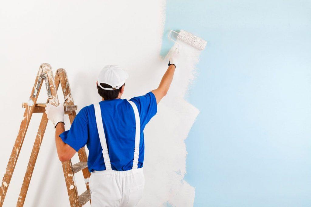 Pintor profesional pintando una pared interior