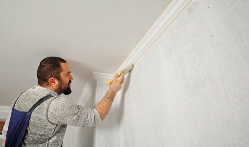 Pintor profesional pintando un muro interior de una casa