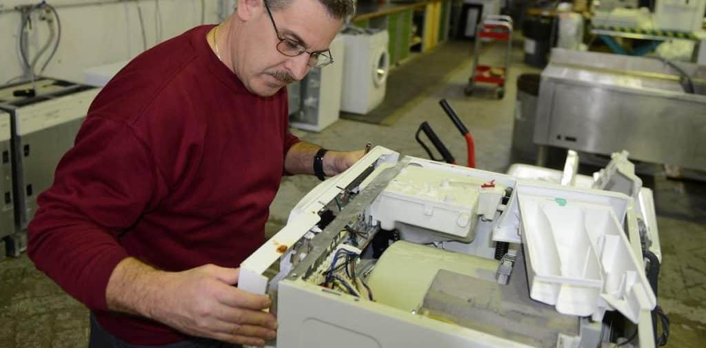 Técnico reparando lavadora en su taller