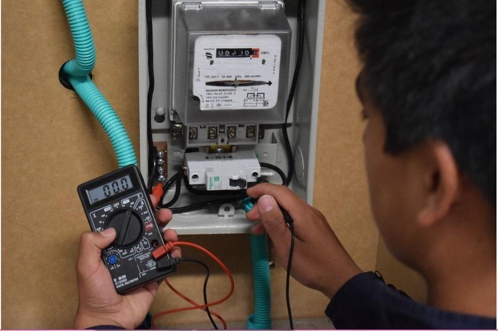 Electricista realizando mediciones en el cuadro eléctrico